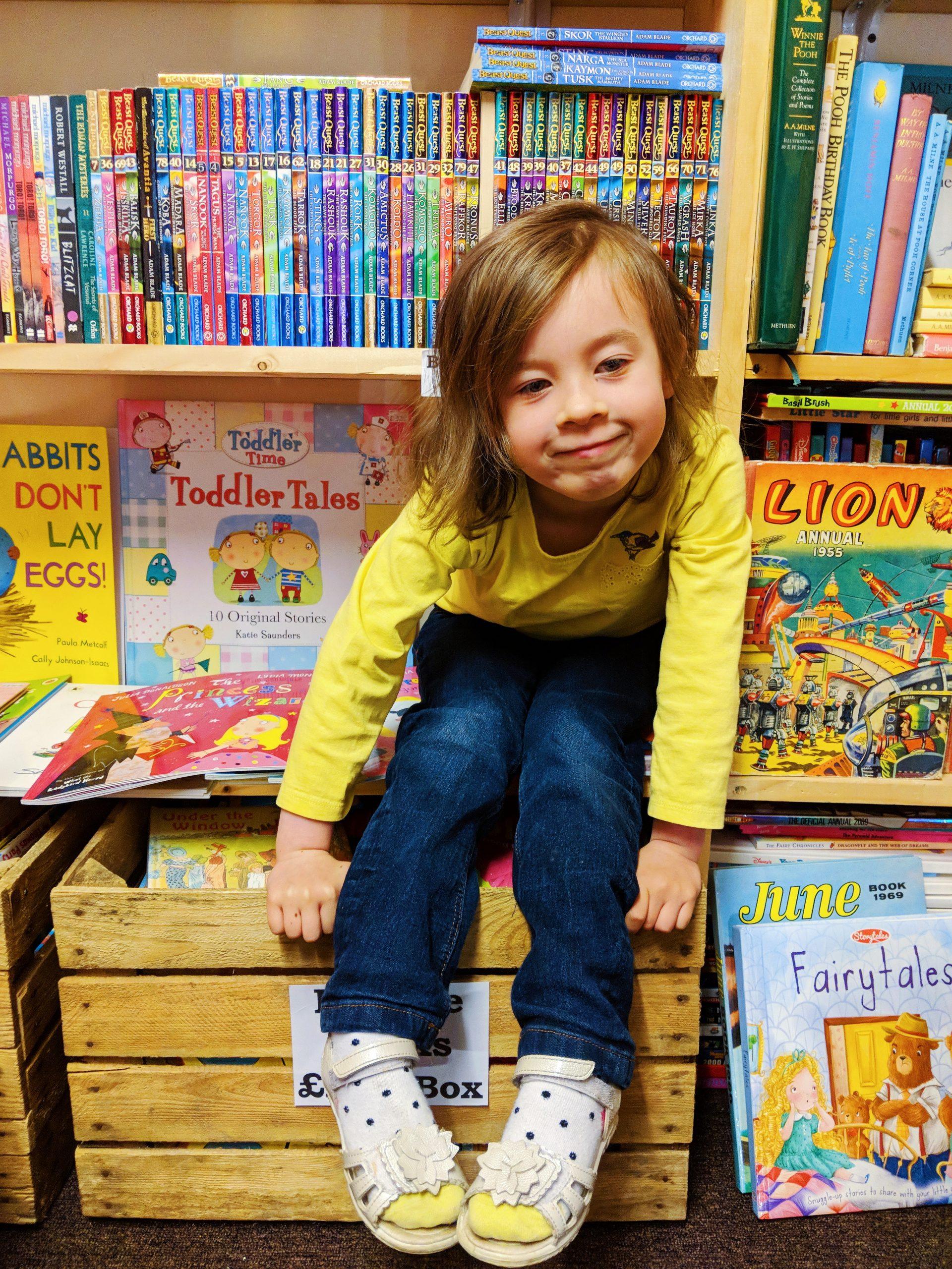 little girl sits in book corner
