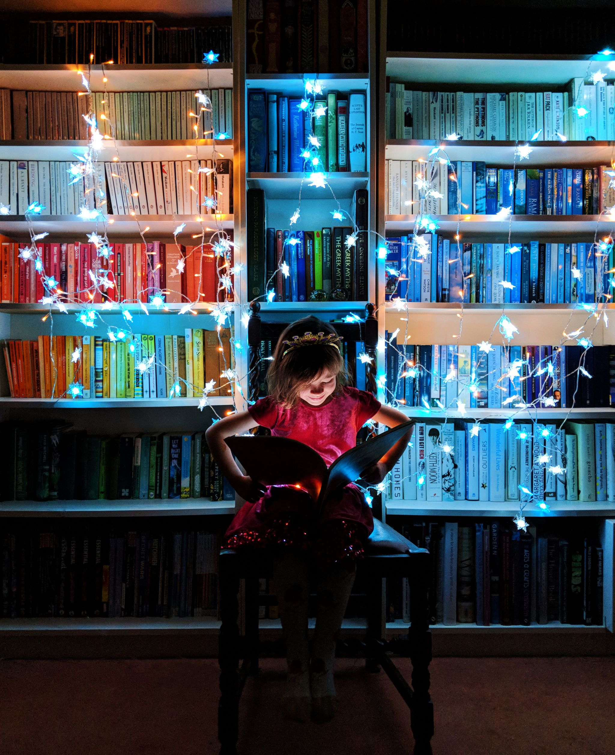 A little girl reading in front of illuminated bookshelves