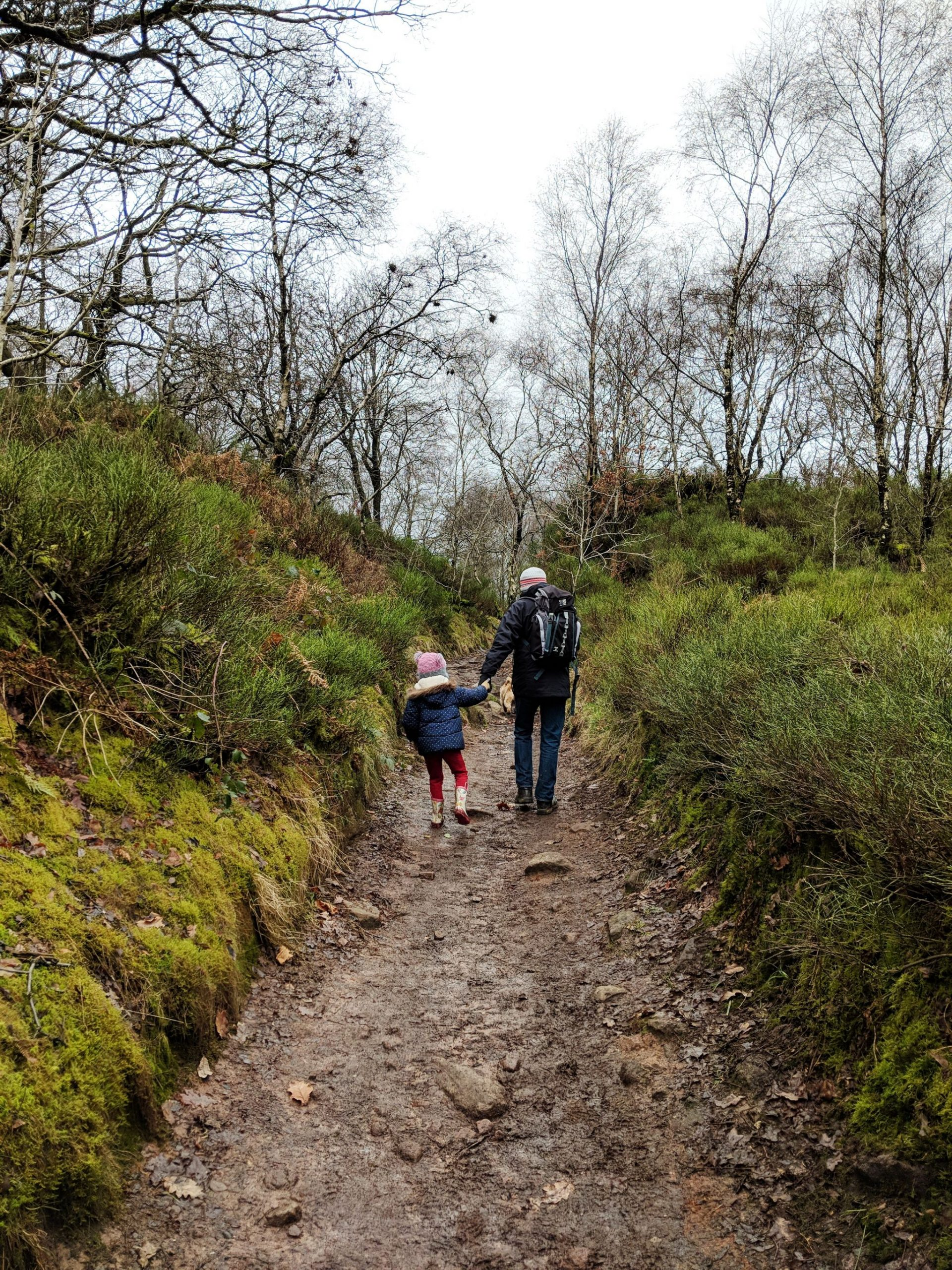 A father and daughter walking along a green path to Lud's Church