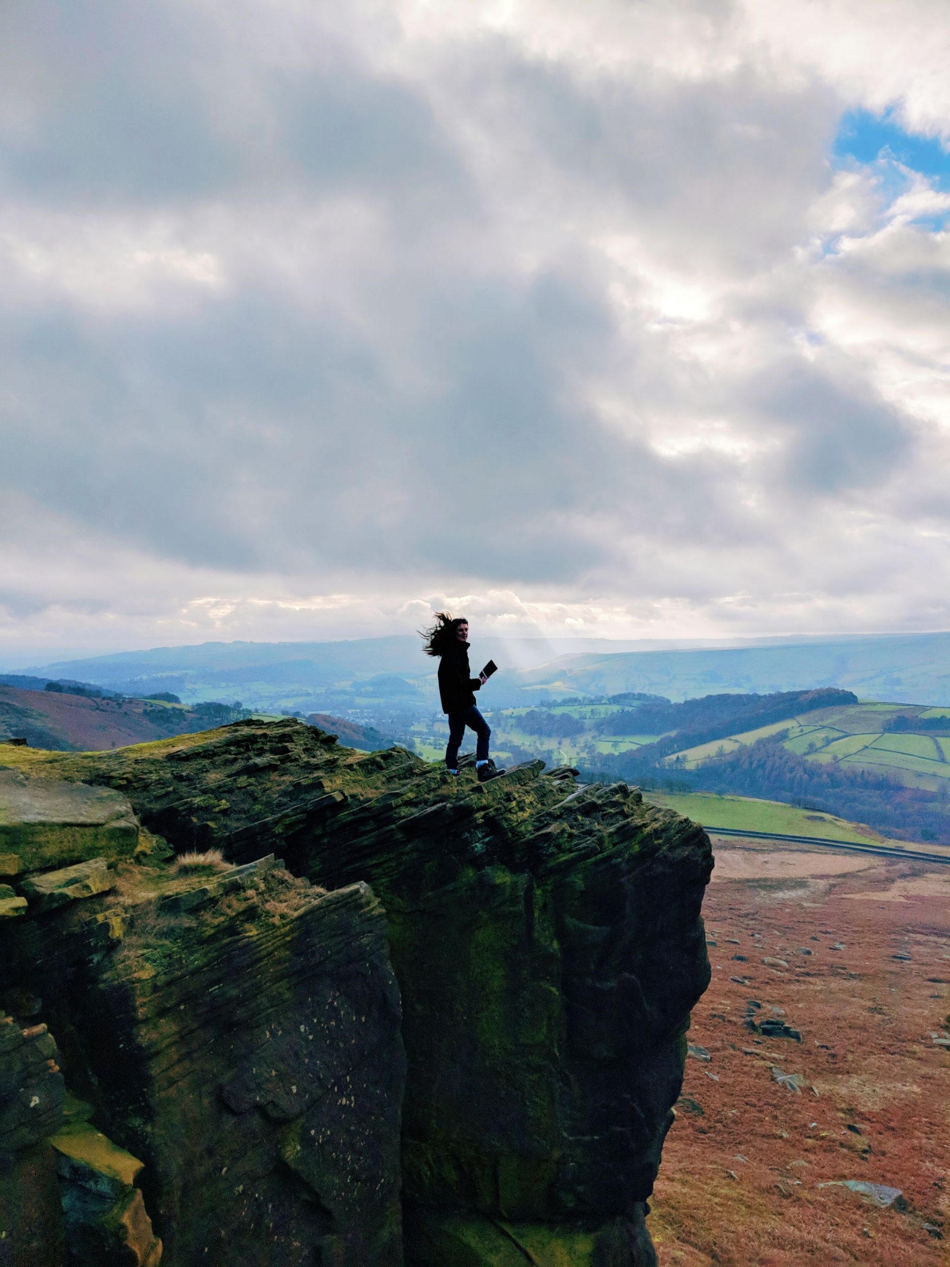 A woman standing on Stanage Edge - Jane Eyre Trail
