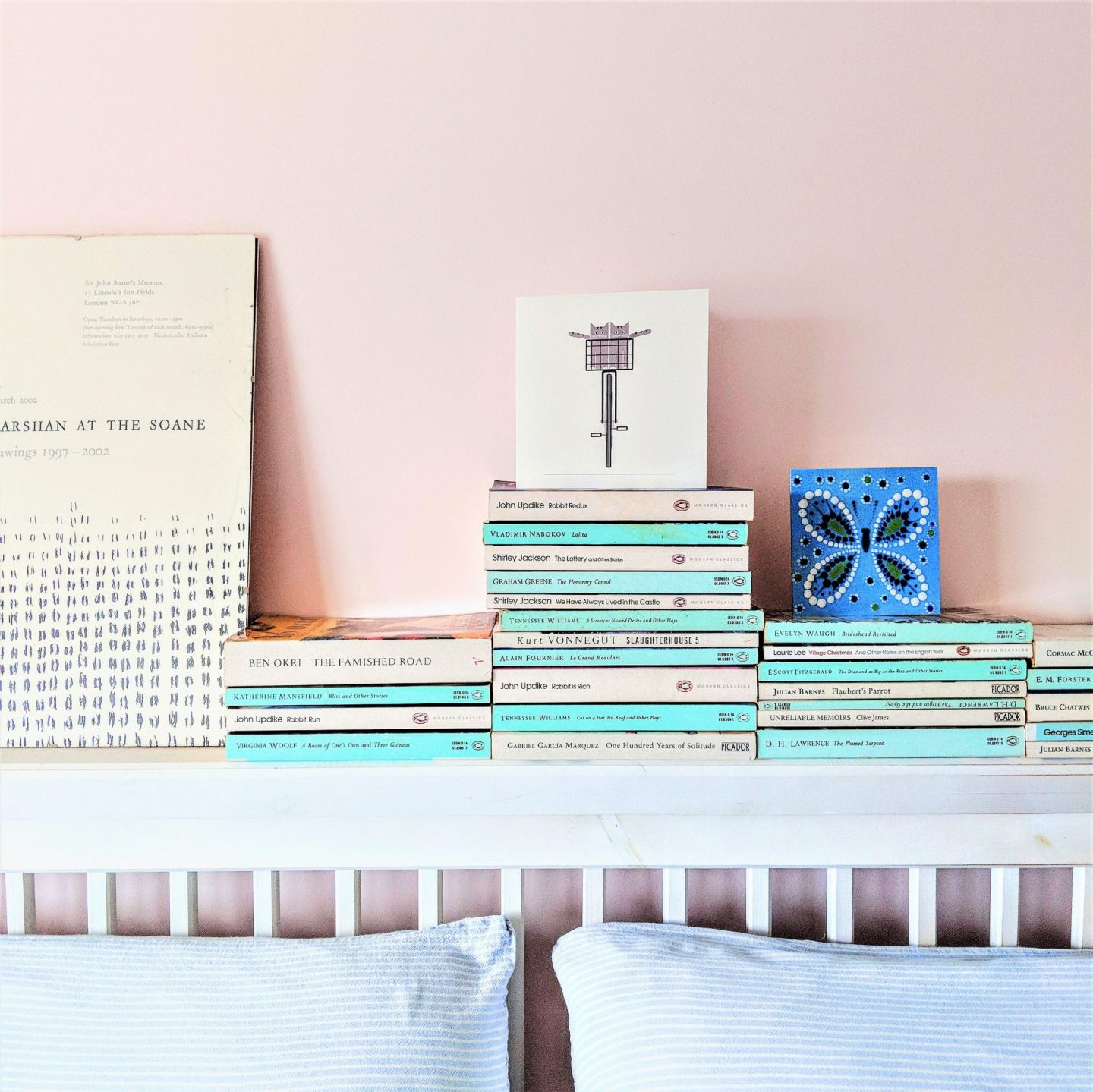 White and aqua books stacked on a shaker bedstead