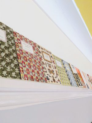 A row of vintage King Penguin Books on a picture rail