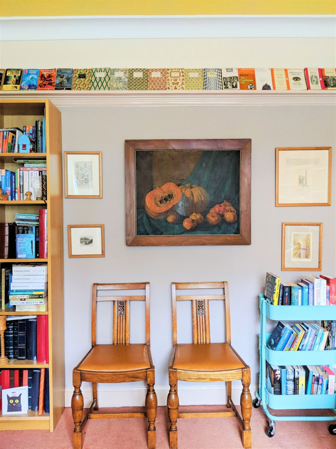 A room with two chairs, a picture rail lined with books and a full book trolley to illustrate creative ways to display books.