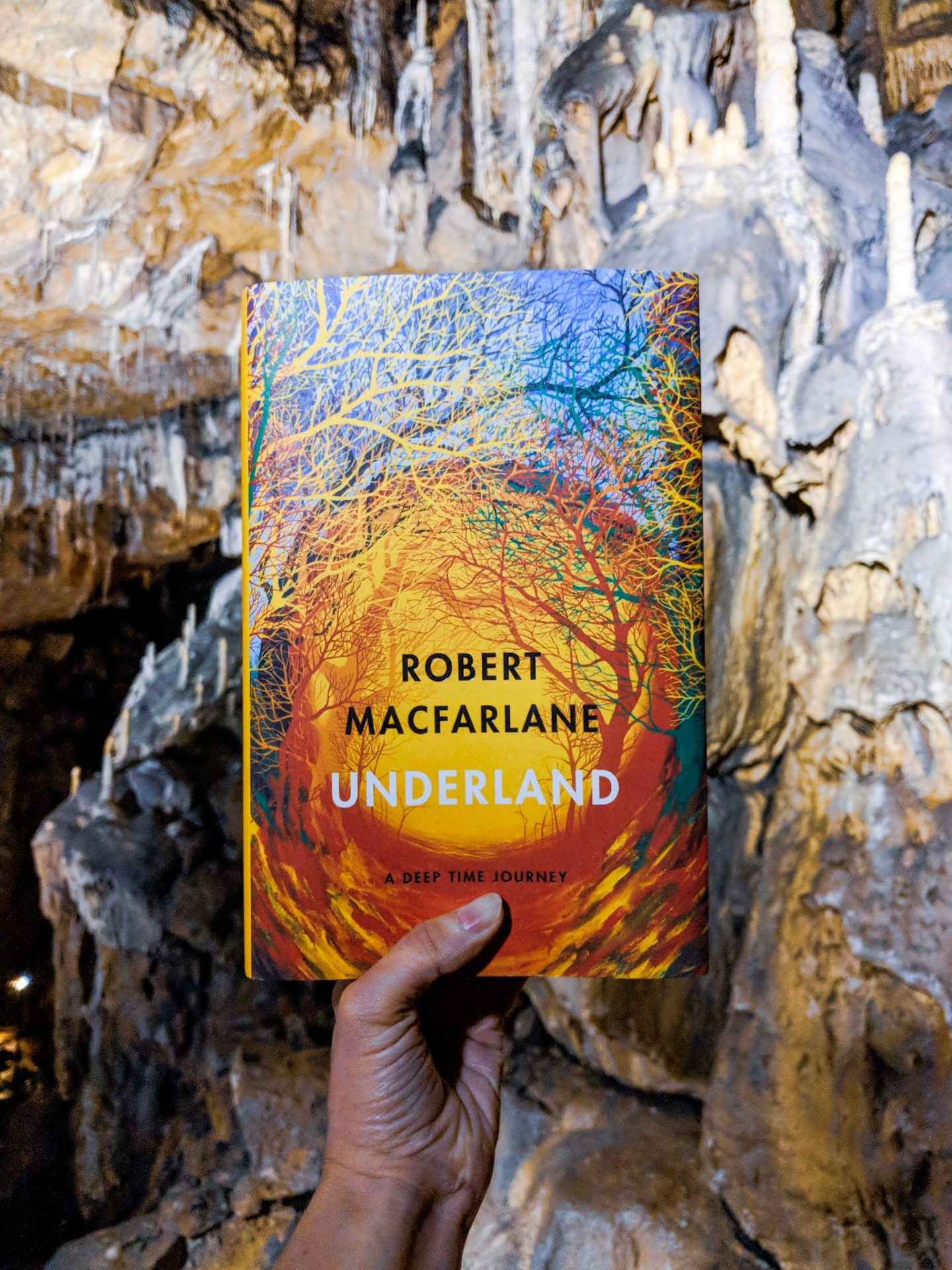 A hand holding Underland by Robert Macfarlane in a cave