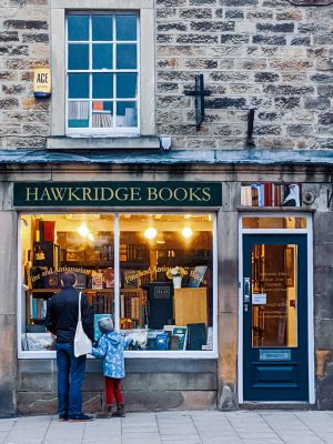 A father and daughter look into a lit window at Hawkridge Books Bakewell