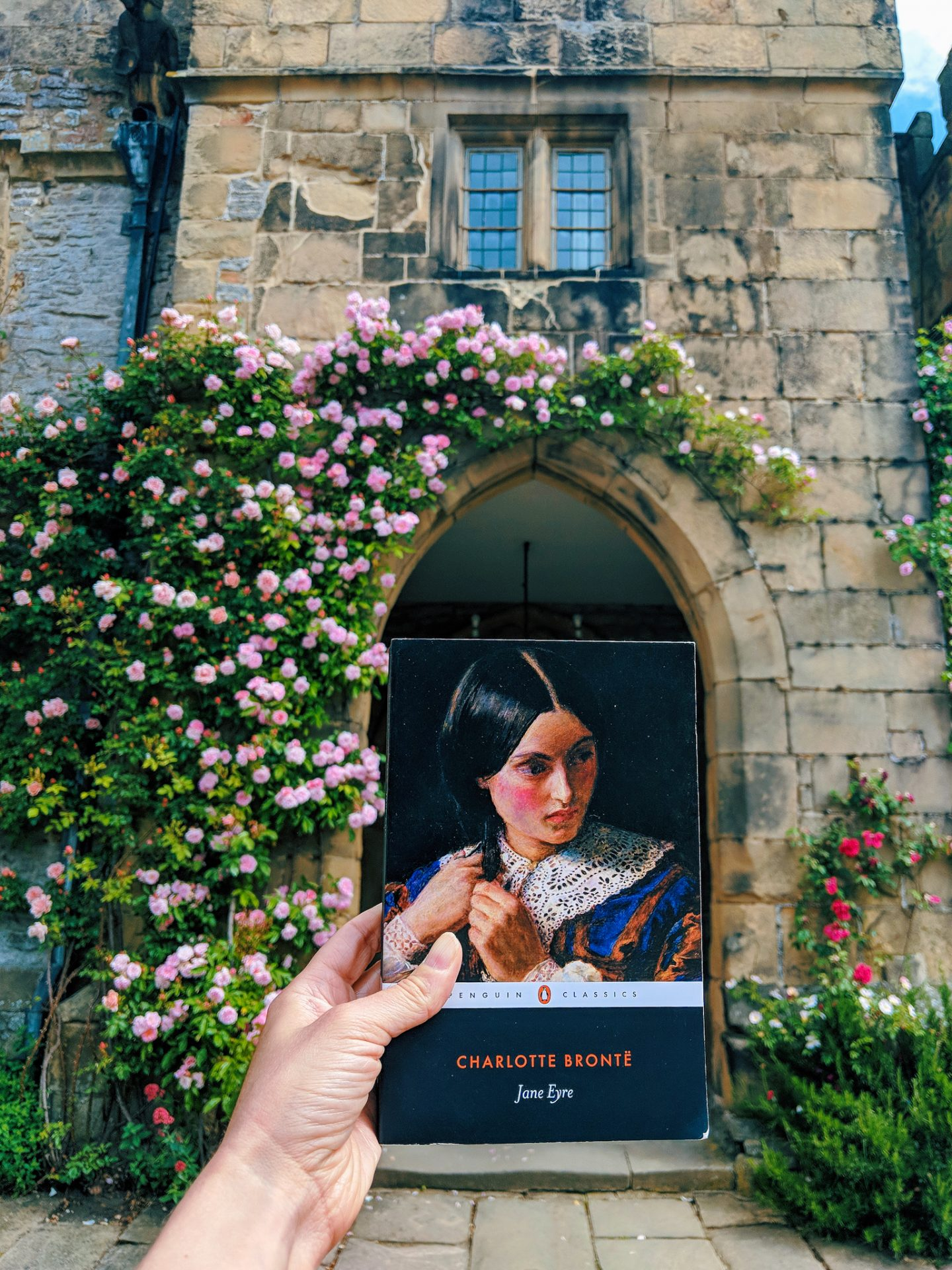 A hand holding up a copy of Jane Eyre by Charlotte Bronte outside Haddon Hall Derbyshire UK