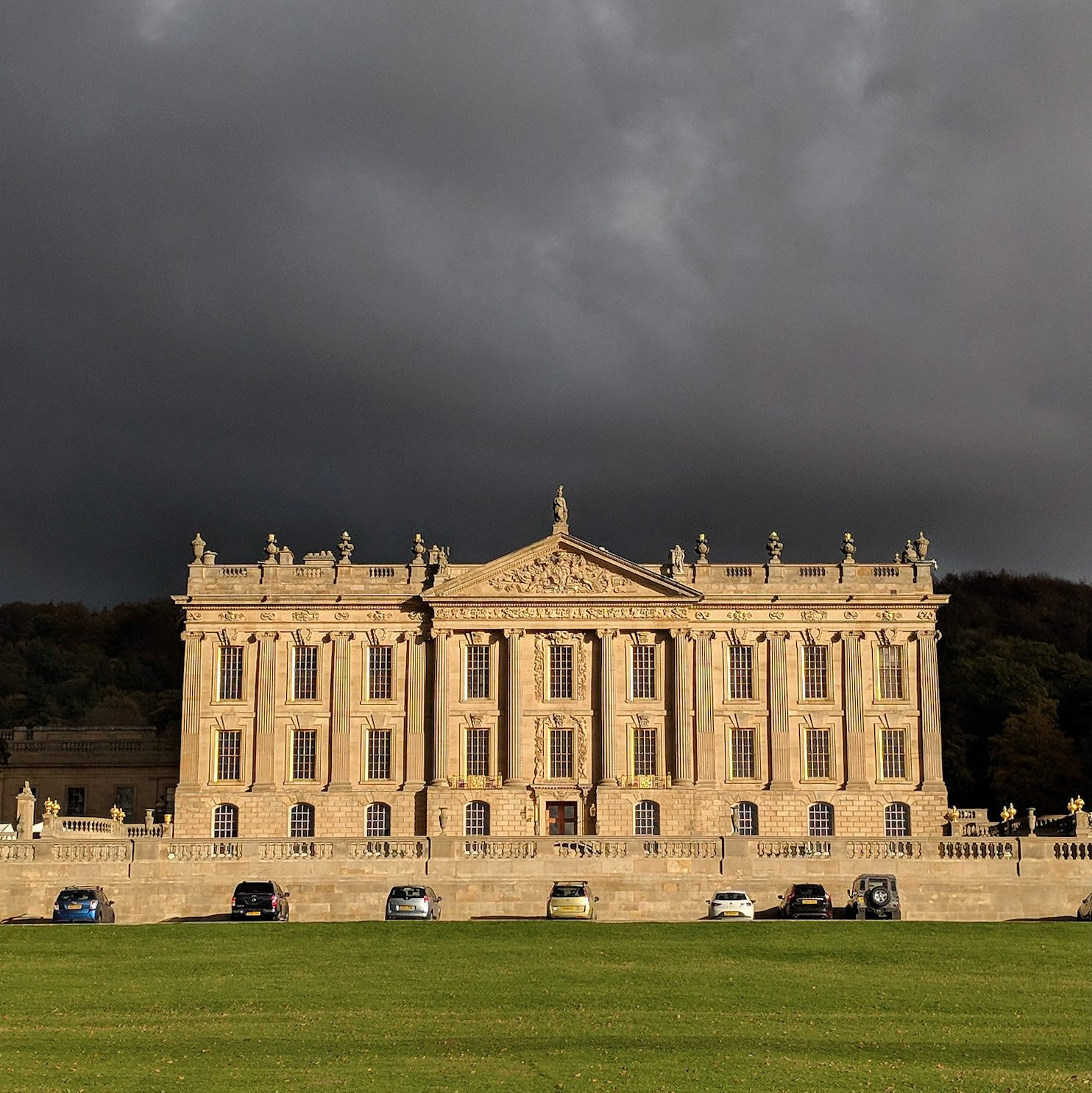 Chatsworth House against a grey stormy backdrop.