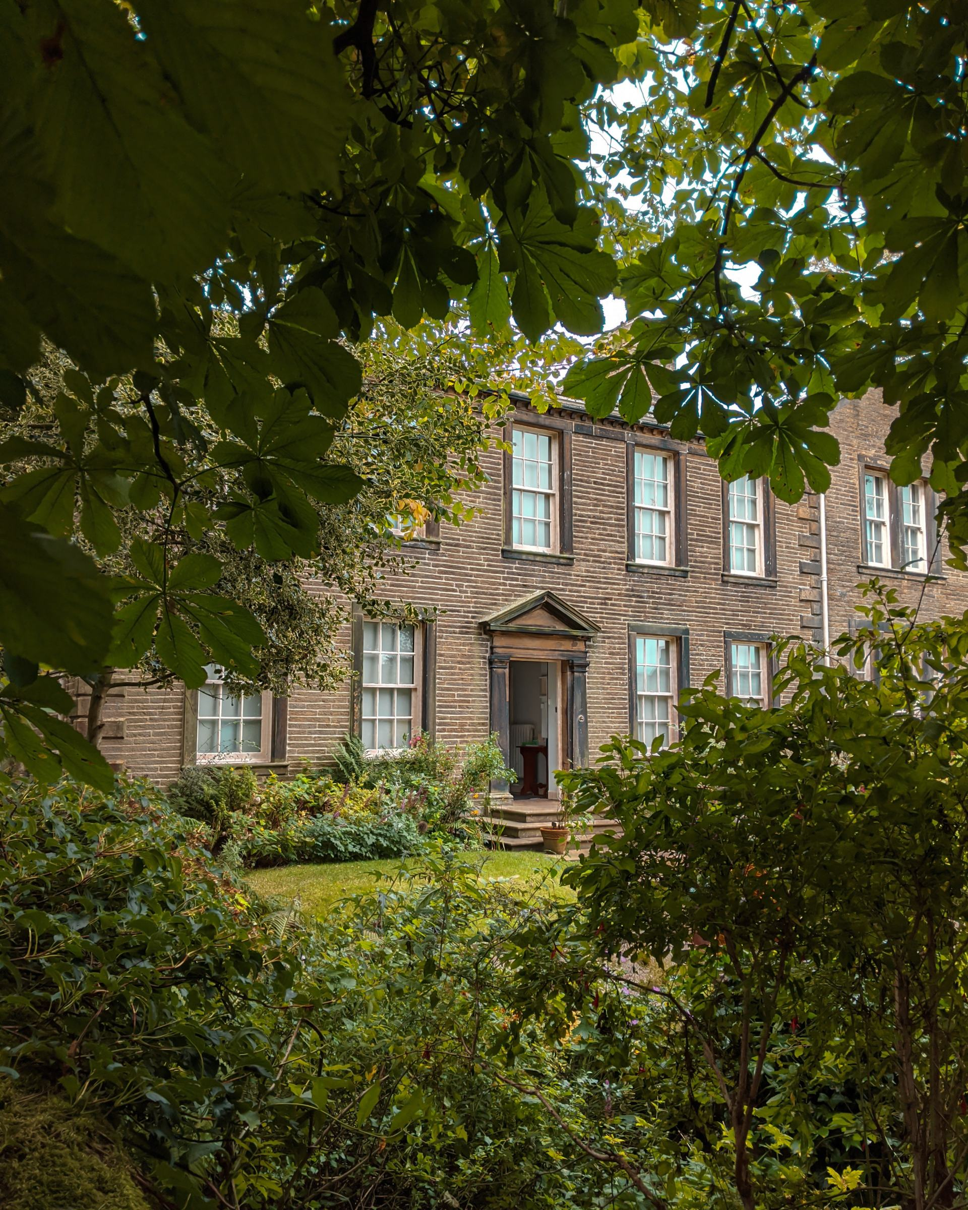 The front of Brontë Parsonage Museum through green leaves.