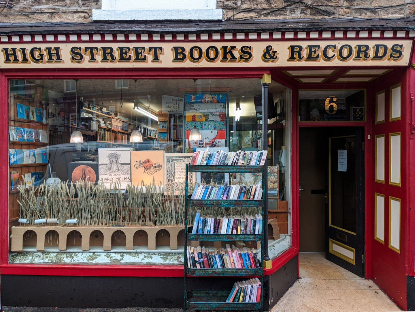 The front window and door of High Street Books and Records in New Mills, Derbyshire. The woodwork is painted in maroon.