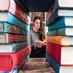 Photo of a female reader as seen through a book window to illustrate bookish lockdown