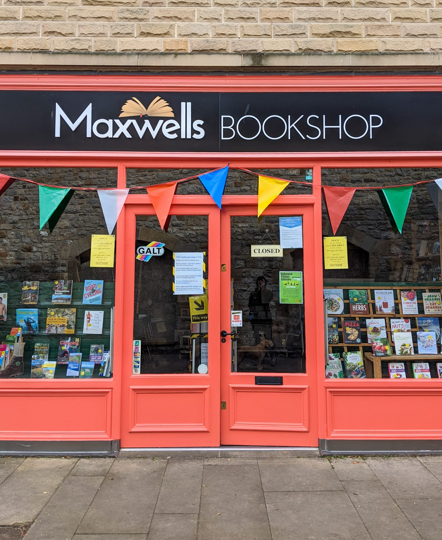 The entrance of Maxwells Bookshop, Bakewell, which is painted red and has bunting hanging above double doors.