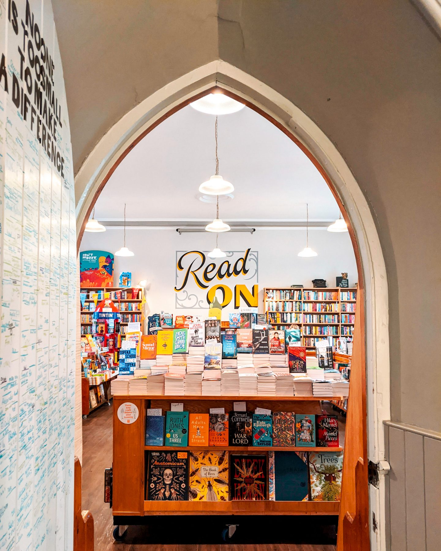 An open doorway looking through to the interior of Forum Books Corbridge Northumberland and a sign painted with the words 'Read On'