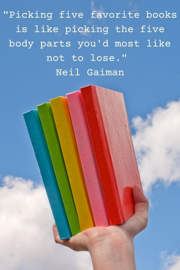 A hand holding up 5 books in the colour of the rainbow against a blue sky to illustrate the Neil Gaiman book quote 'Picking five favorite books is like picking the five body parts you'd most like not to lose.'