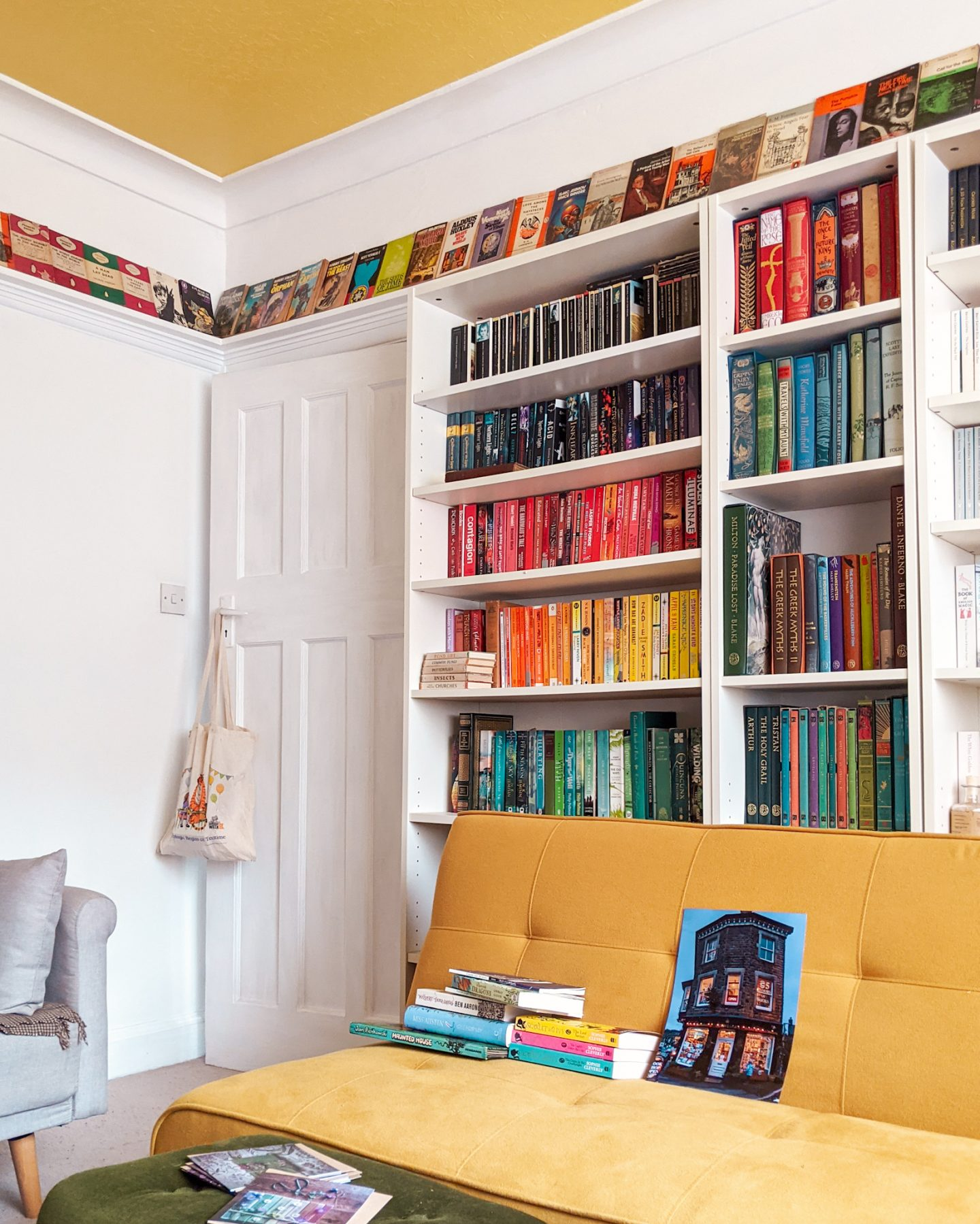 A colourful home library with a yellow ceiling, white bookshelves filled with rainbow books and a yellow sofa.