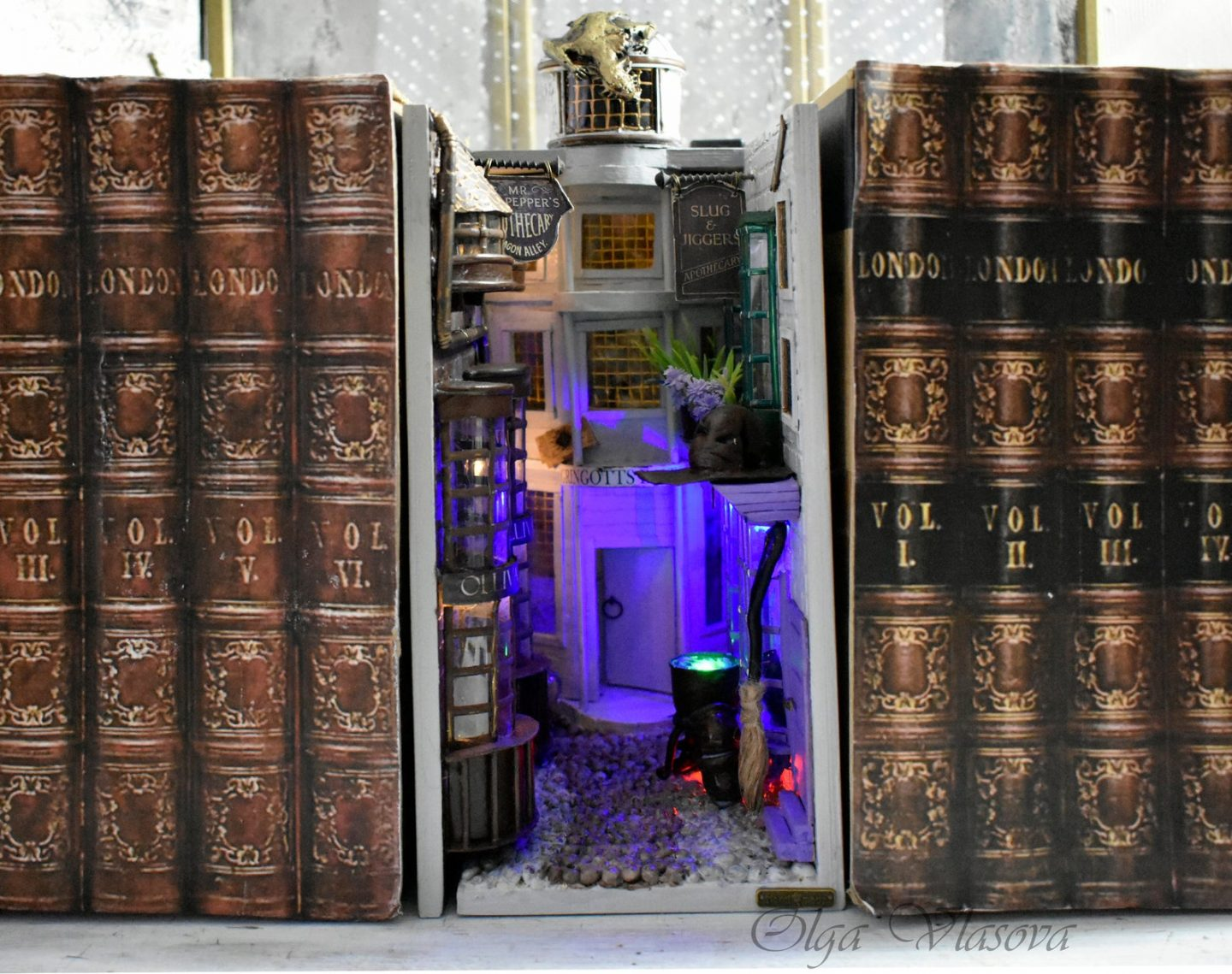 A bookshelf diorama of Diagon Alley between rows of books