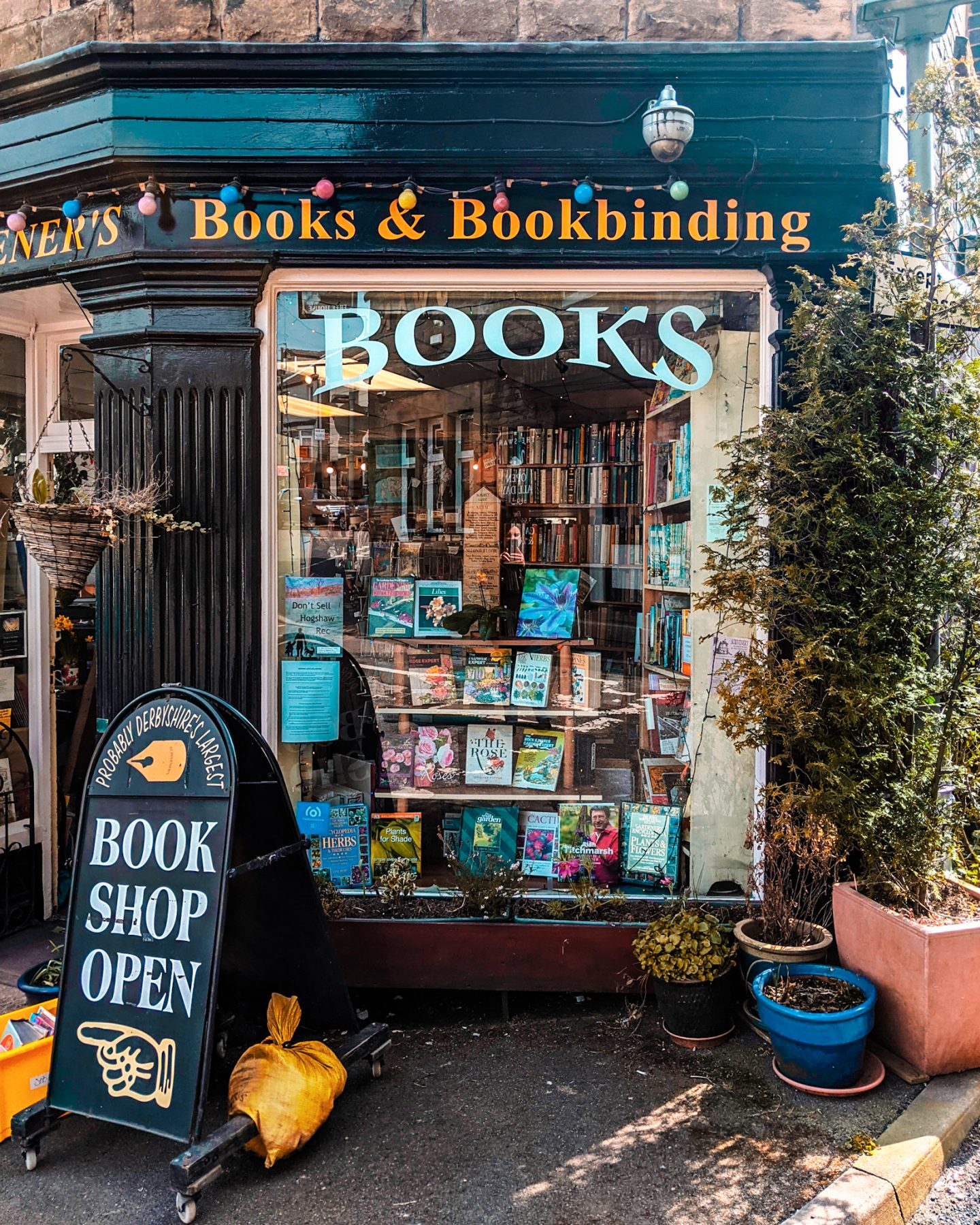 A full-size window at Scriveners Bookshop Buxton with a sign reading Book Shop Open