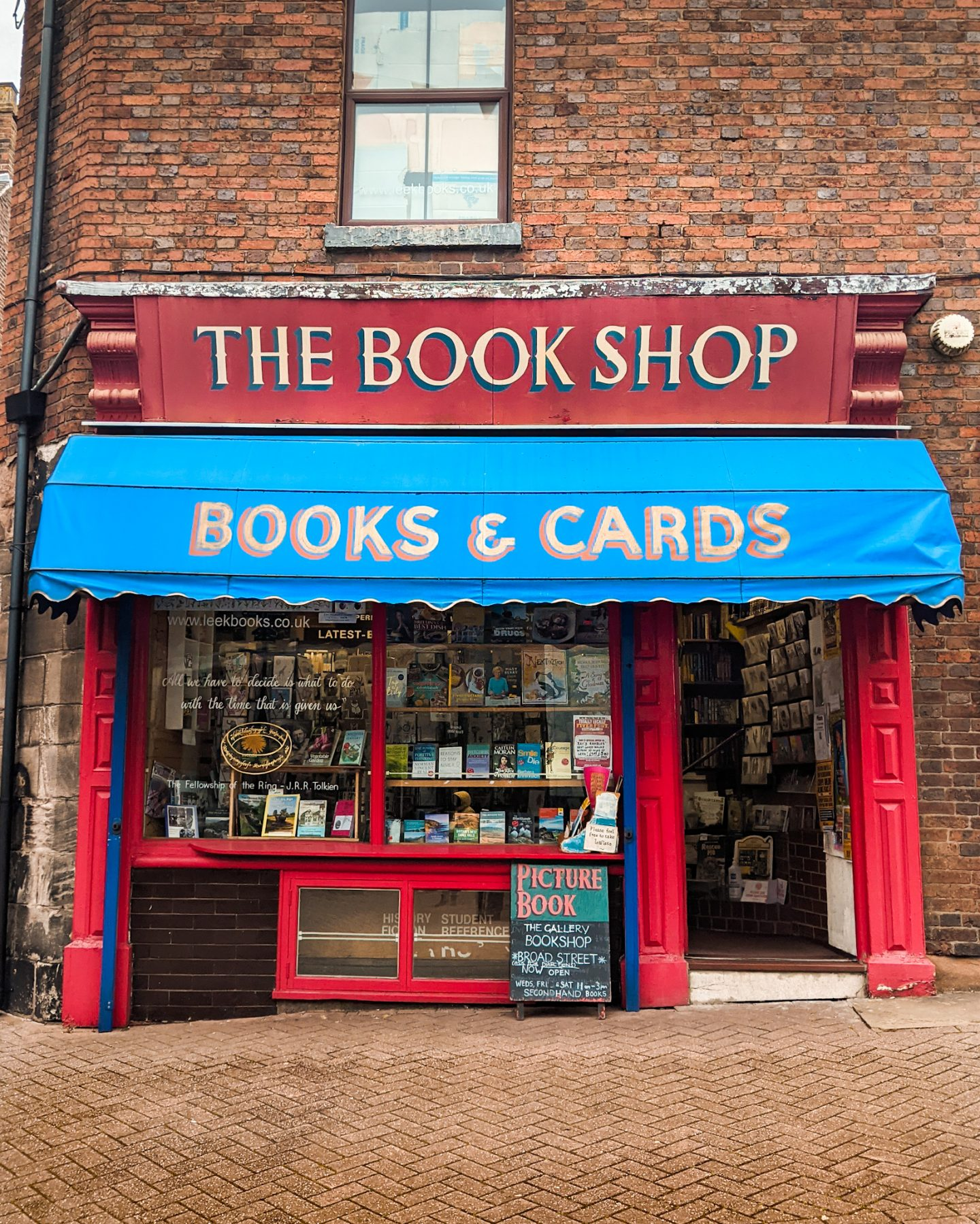 The exterior of Picture Book Bookshop with a red window frame and door and a blue awning