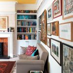 A home library with a yellow ceiling and a picture gallery along one wall