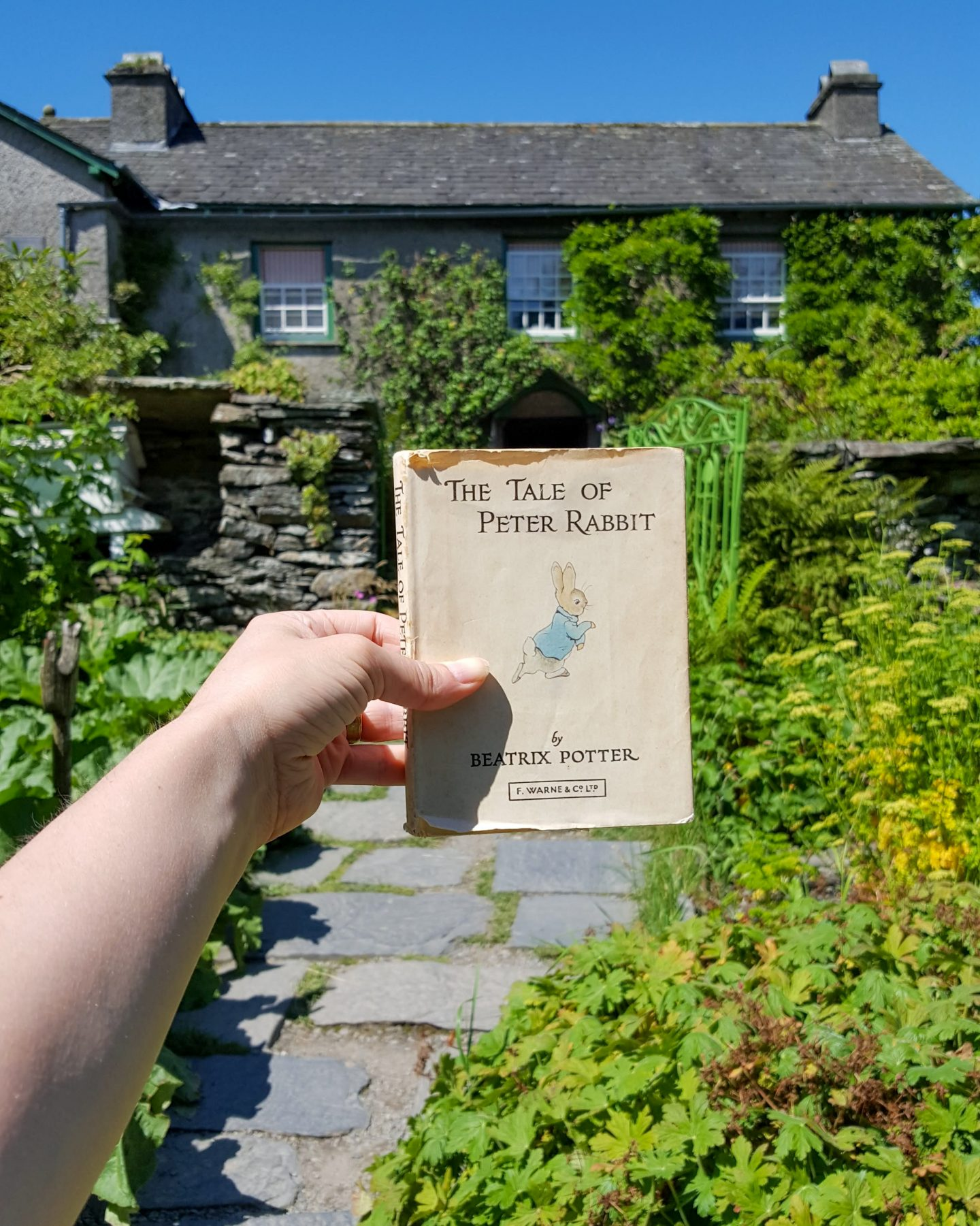 A person holds an old copy of The Tale of Peter Rabbit in front of Hill Top, Beatrix Potter's House, Lake District