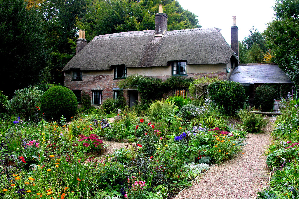 A image of the front of Thomas Hardy's Cottage with thatched roof and traditional cottage garden in bloom