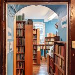 A view through a chipped wooden door frame and a blue-painted arch to a bookshop full of bookshelves