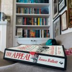 A copy of The Appeal by Janice Hallett with a bookshelf in the background